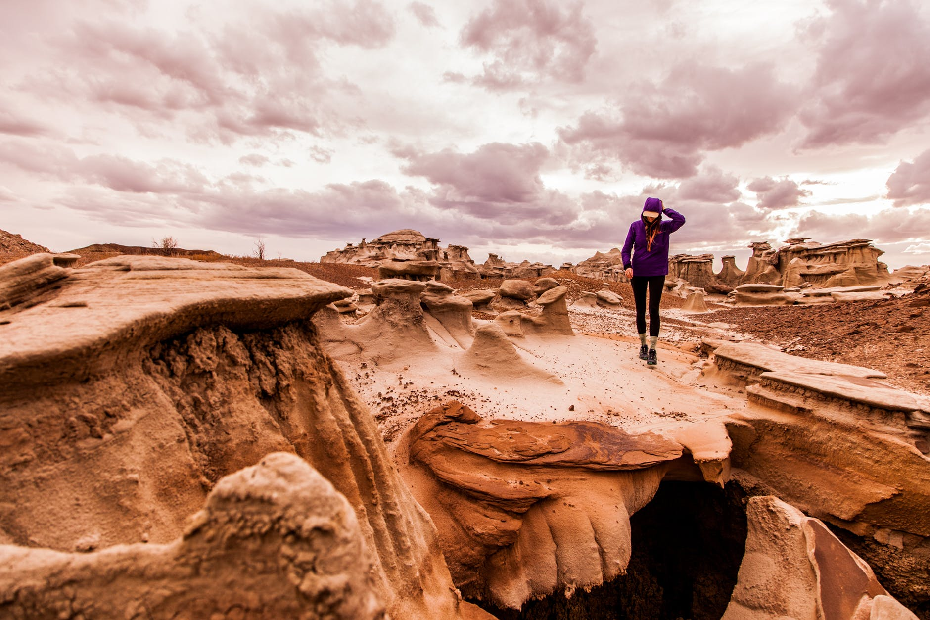 person walking on rock formation under cloudy sky